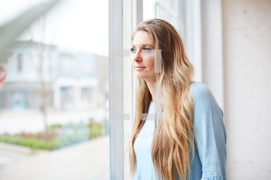 a young woman standing in front of a window