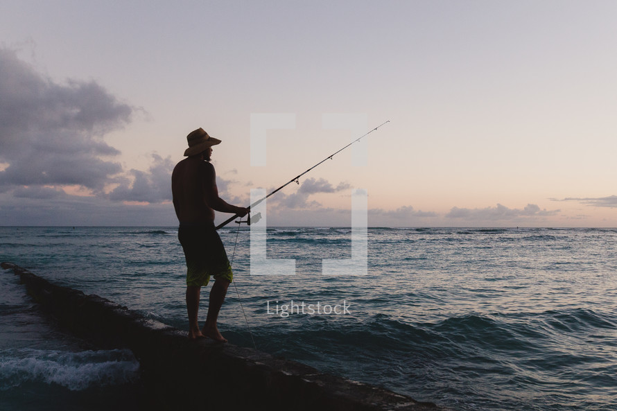 silhouette of a fisherman standing on a rock holding a fishing pole