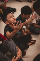 children sitting on the floor with raised hands