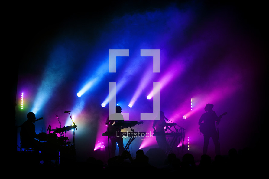 blue and purple stage lights on a band on stage at a concert