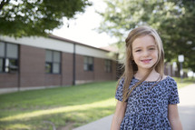 A smiling little girl standing in front of a school.