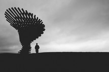 silhouette of a man standing next to a sculpture