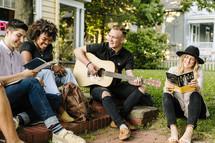man playing a guitar outdoors at a Bible study