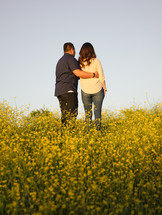 a couple standing in a field of yellow wildflowers