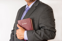 man in a suit holding a BIble