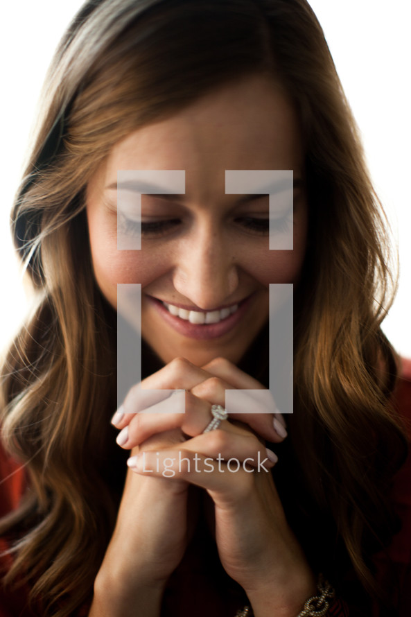 A smiling young woman with her hands clasped in prayer.