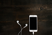 iPhone with earbuds on a wooden table