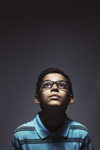 Young kid with glasses looking up.