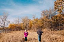 man and woman walking along a lake shore in fall