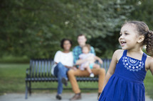 family sitting on a park bench outdoors  and a toddler girl in pigtails