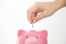 person placing a coin in a piggy bank