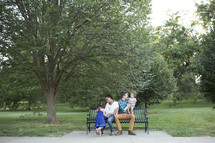 family sitting on a park bench outdoors