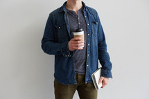 a man holding a coffee cup and a Bible at his side