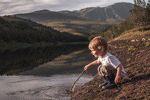 a toddler boy playing with a stick in a pond