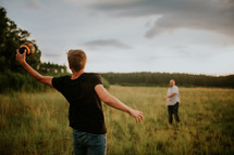 father and son throwing and catching a football in a field