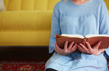 a woman sitting on the floor reading a Bible