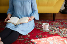 a woman sitting on a rug reading a Bible