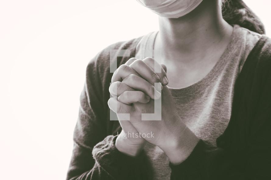 a woman praying wearing a mask