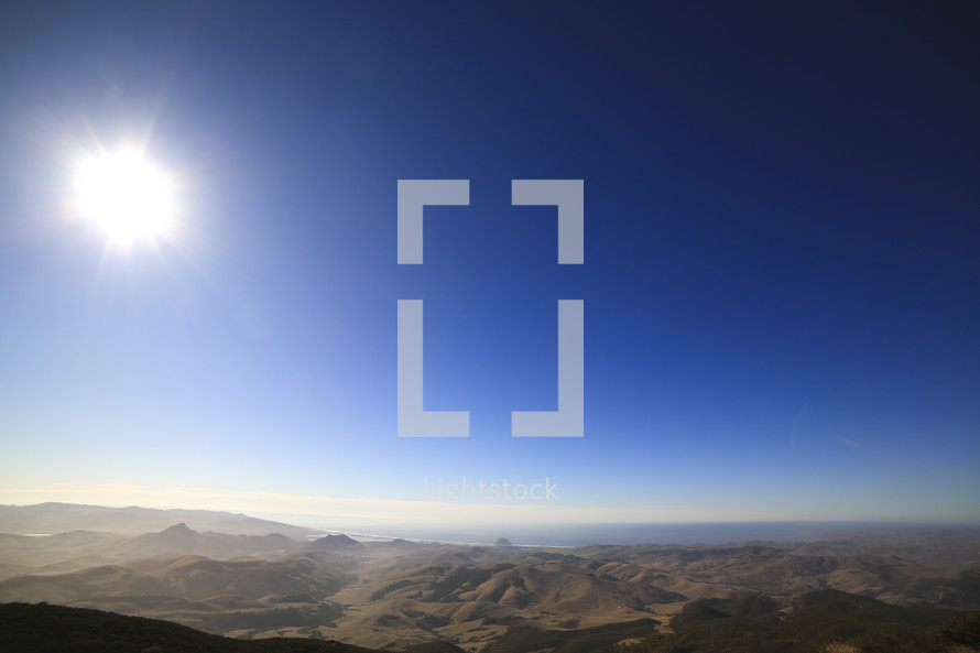 A sunburst over a mountain range.