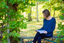 a woman sitting on a bench outdoors reading a Bible
