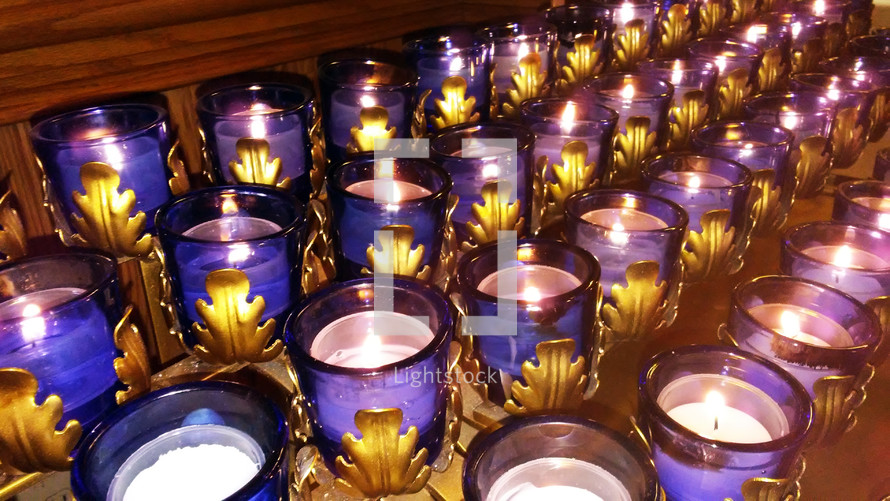 Four Rows of Candles burning during a prayer vigil at church during a candle light service where the congregation is invited to worship and pray and meditate on the presence of God.