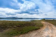 gravel road near a lake