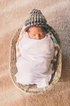 newborn sleeping in a basket