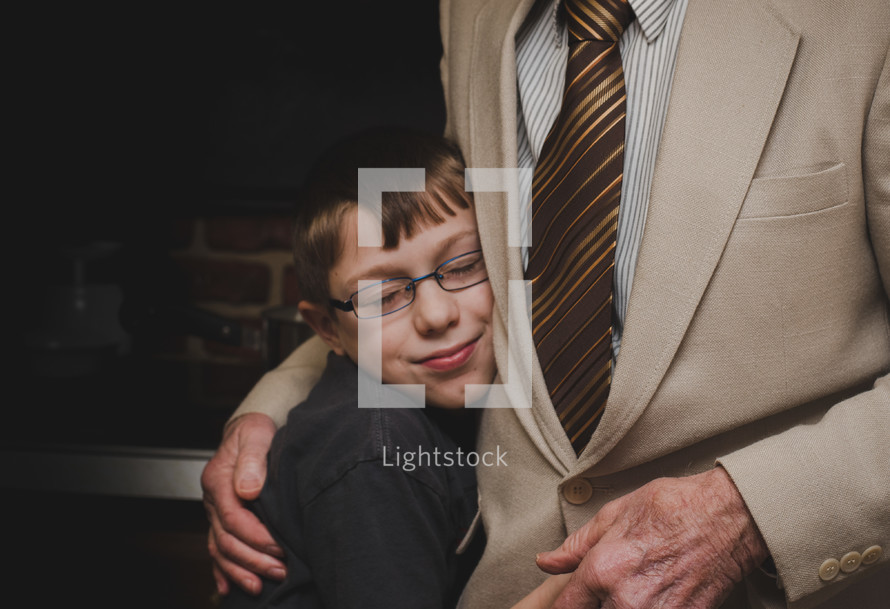 child hugging his grandfather