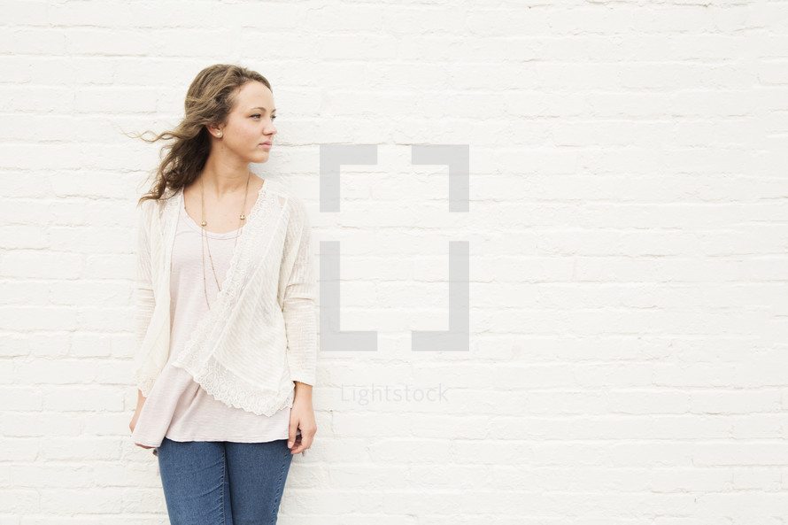 portrait of a young woman standing against a white wall and thinking.