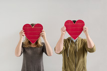 a couple holding up red wooden hearts covering their faces