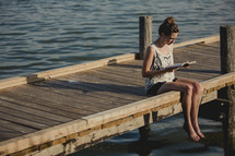 girl reading a Bible with her feet in the water