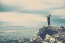 man standing on sea rocks with his hands raised in worship to God
