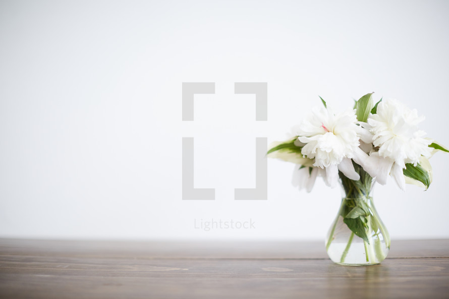 vase of white flowers on a wood table