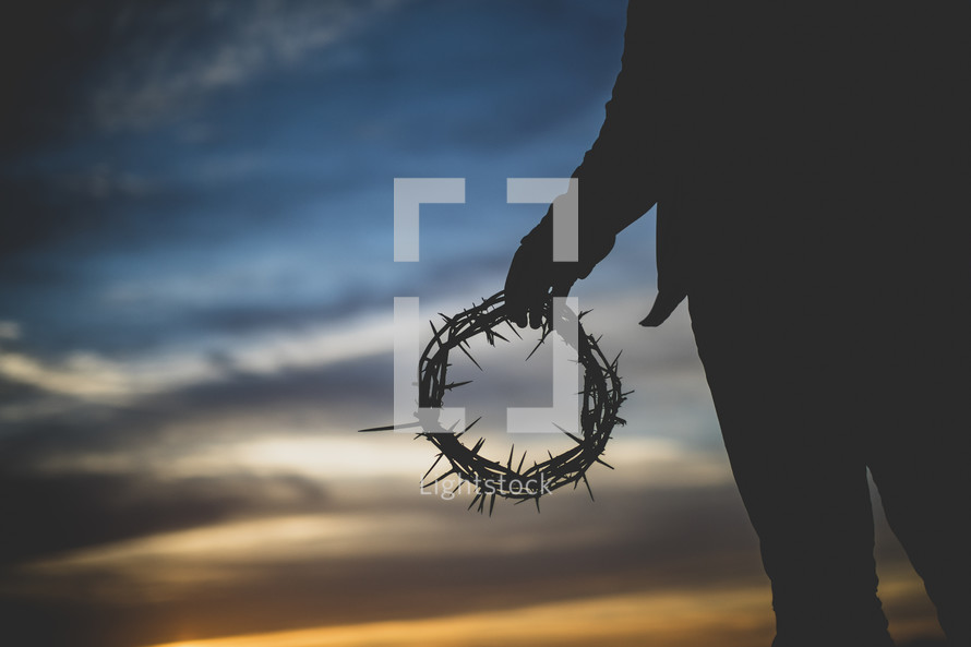 silhouette of a man holding a crown of thorns at sunset