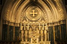 Candles at an ornate church altar.