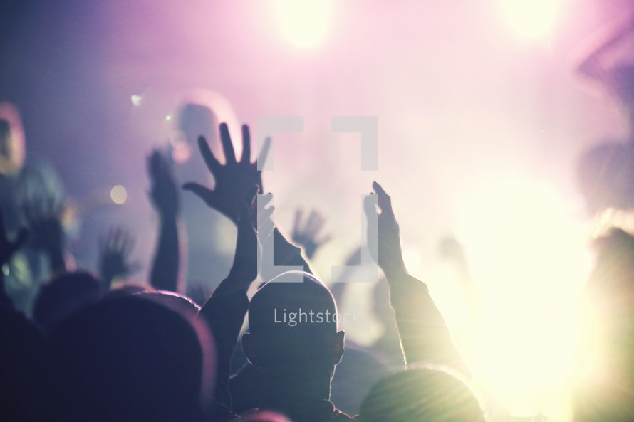 Hands raised in worship with lens flare