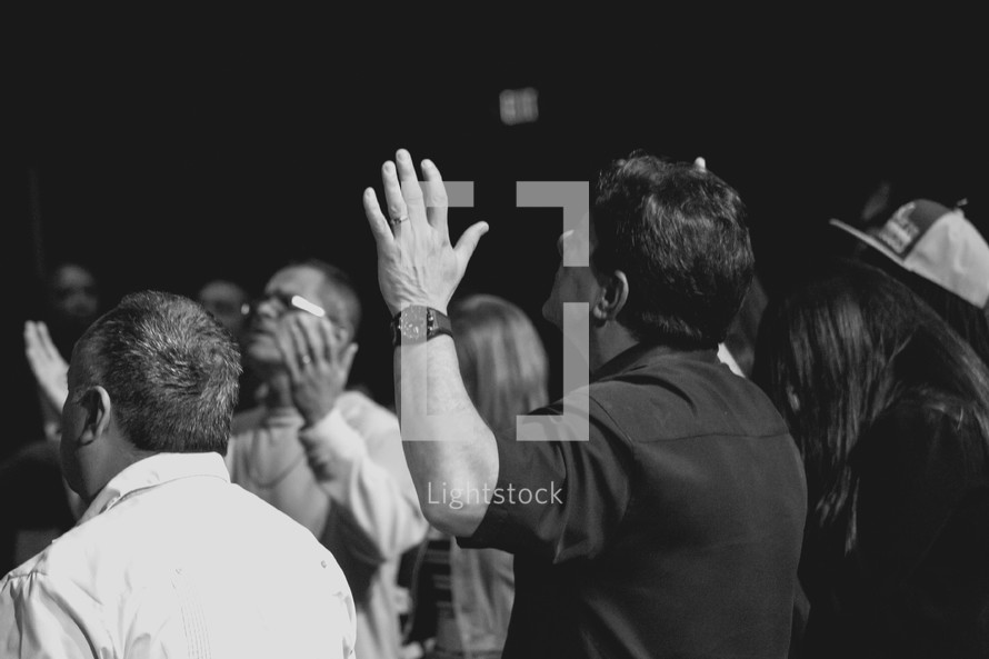 men with raised hands during a worship service