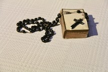 Prayer rosary and Christian cross on an old Bible