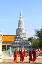 Buddhist monks walking in front of a temple