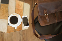 leather computer bag in a chair and iPhone and coffee mug on a table