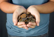 A young girl holding out a pile of coins