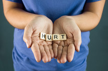 """A young girl holds out the word """"Hurt"""""""
