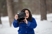 a woman in a coat taking a picture of snow