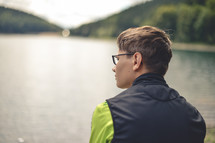 a young man looking out at lake water