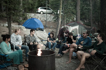 A group of campers sitting around a campfire in the forest.