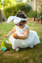 toddler girl with an Easter basket and bunny ears wearing an Easter dress