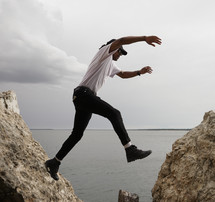 a man leaping between rocks