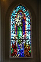 Stained glass window depicting Mary, Baby Jesus, and worshippers.
