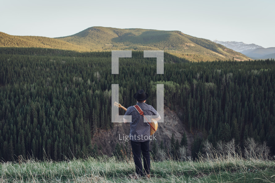 man with guitar in the mountains