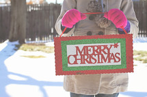 a woman holding a Merry Christmas sign